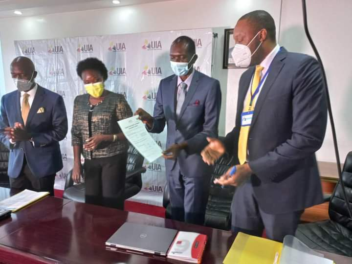 Professor Patrick Ogwang (Center), the developer of Covidex, displays a free investment licence given to him by government alongside five acres of land at Soroti Industrial park to set up a factory.